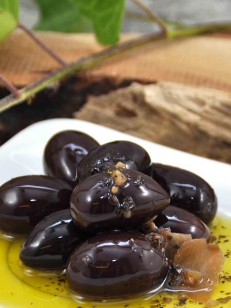 Schwarze Bio Oliven - mit Stein - in Olivenöl mit Kräutern und Knoblauch